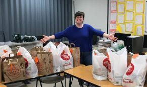 Rachel Ewen, ReWA Elementary Instructor stands with bags of collected supplies for Elementary families preparing for difficult weeks ahead.