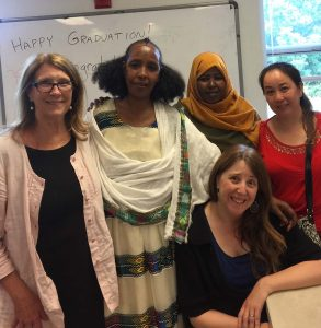 A group of five women representing ESL volunteers, teacher and students, smiling at the camera.