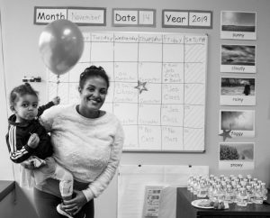 Woman smiling with toddler holding a balloon at ReWA's SeaTac Open House party.