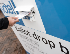 ballot being delivered into ballot drop box