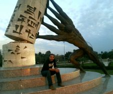 Dr. Azmi Jaafar in Baghdad in front of statue of stone figure with four arms putting a column in place